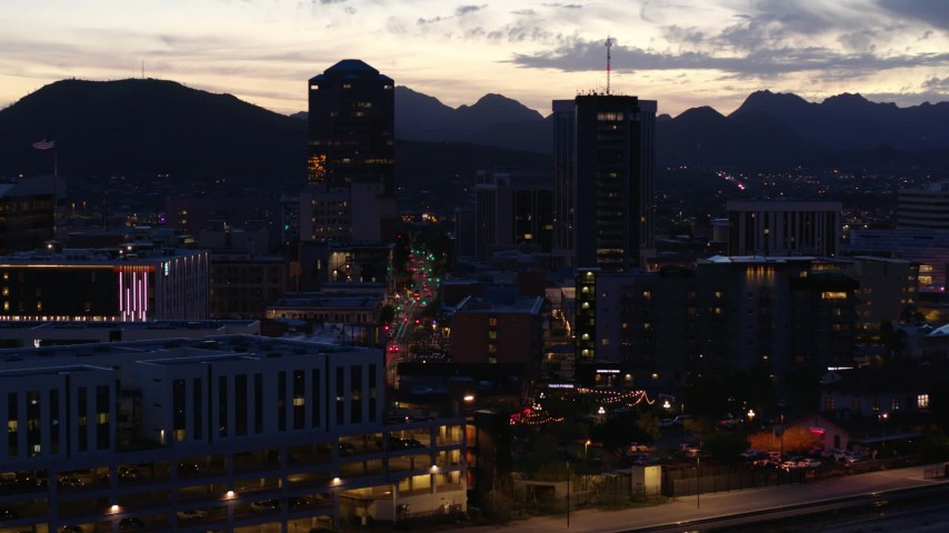 5.7K stock footage aerial video reverse view of tall office towers at sunset, mountain range in background, Downtown Tucson, Arizona Aerial Stock Footage | DX0002_147_029