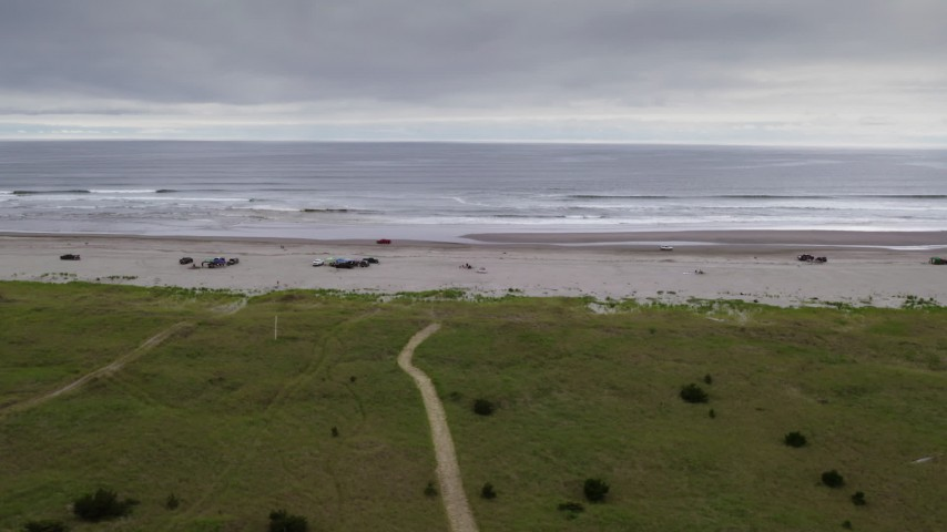 4K stock footage aerial video track a truck passing groups of people enjoying the beach in Long Beach, Washington Aerial Stock Footage | DX0002_148_002