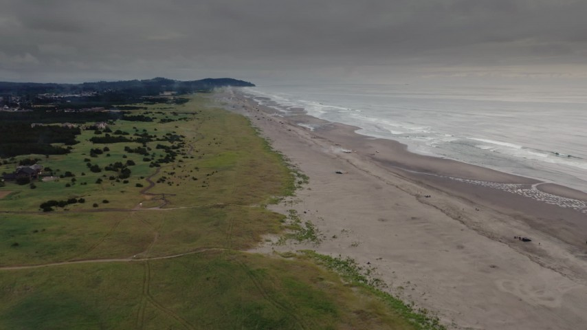 4K stock footage aerial video of a reverse view of beach-goers near the ocean in Long Beach, Washington Aerial Stock Footage | DX0002_148_020