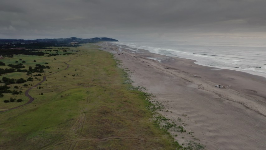 4K stock footage aerial video of a reverse view of beach-goers and fireworks near the ocean in Long Beach, Washington Aerial Stock Footage | DX0002_148_022
