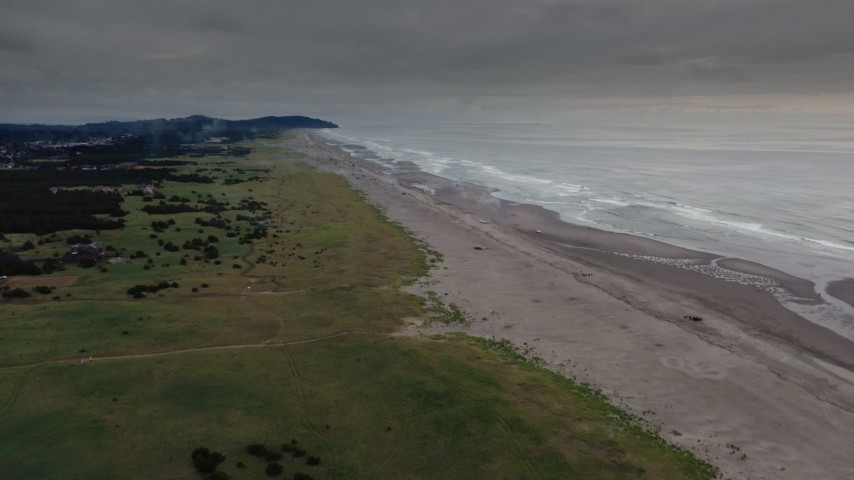 4K stock footage aerial video of a reverse view of groups of beach-goers near the ocean in Long Beach, Washington Aerial Stock Footage | DX0002_148_023