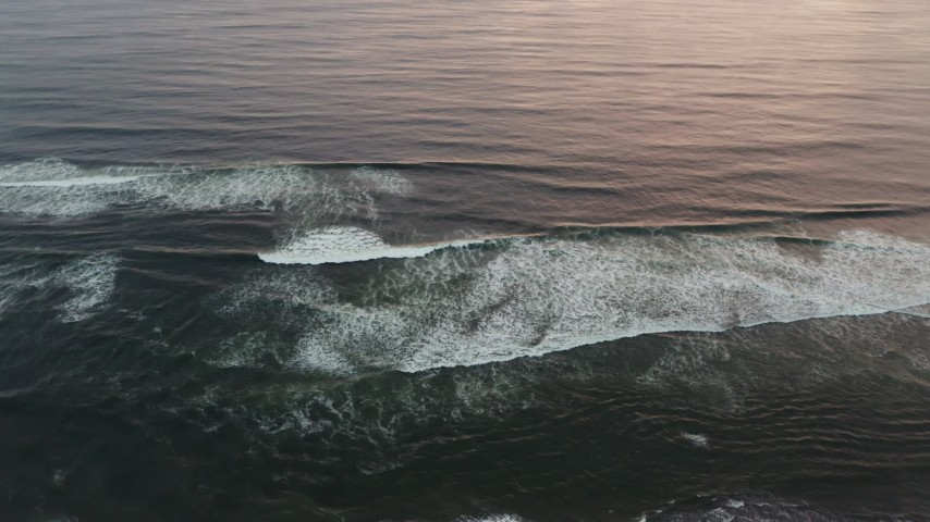 4K stock footage aerial video of flying away from ocean waves to reveal the beach at sunset, Long Beach, Washington Aerial Stock Footage | DX0002_148_025