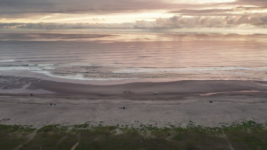4K stock footage aerial video of flying away from beach and ocean waves, tilt to focus on clouds at sunset in Long Beach, Washington Aerial Stock Footage | DX0002_148_026