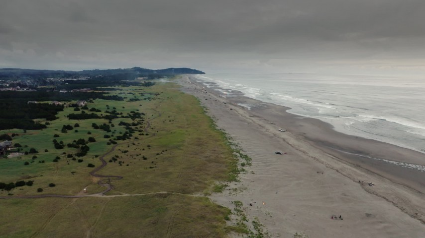 4K stock footage aerial video of the beach, ocean waves, and fireworks at sunset in Long Beach, Washington Aerial Stock Footage | DX0002_148_030