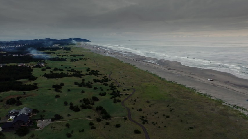 4K stock footage aerial video fly toward the beach as fireworks go off at sunset in Long Beach, Washington Aerial Stock Footage | DX0002_148_036
