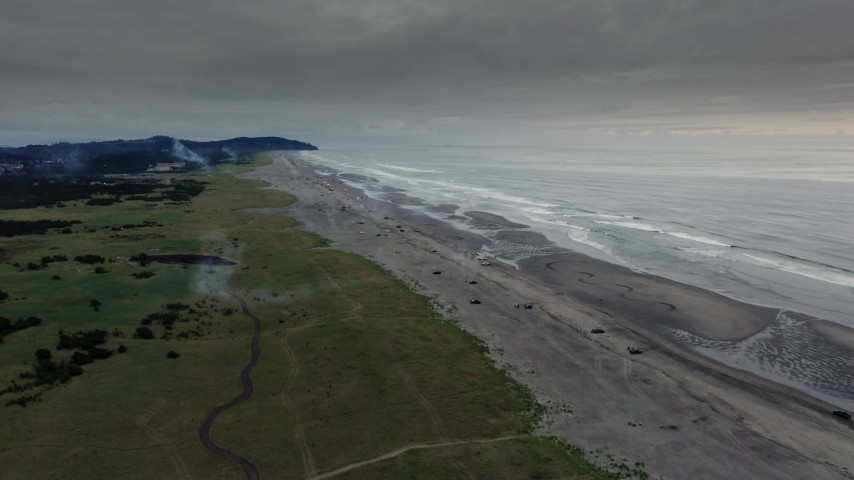 4K stock footage aerial video reverse view of the beach as fireworks go off at sunset in Long Beach, Washington Aerial Stock Footage | DX0002_148_038