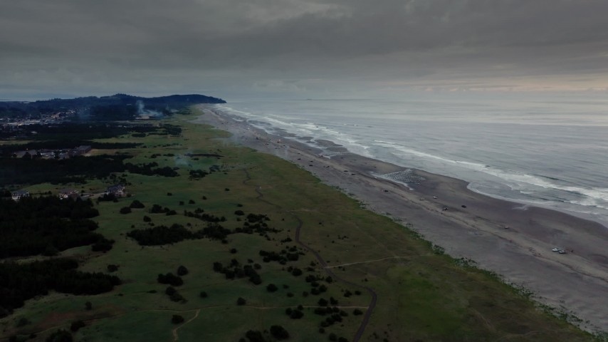4K stock footage aerial video fly away from the beach revealing fireworks at sunset in Long Beach, Washington Aerial Stock Footage | DX0002_148_039