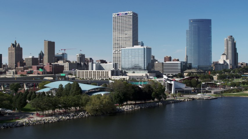 5.7K stock footage aerial video of tall skyscrapers seen while flying by a waterfront outdoor stage in Downtown Milwaukee, Wisconsin Aerial Stock Footage | DX0002_149_031