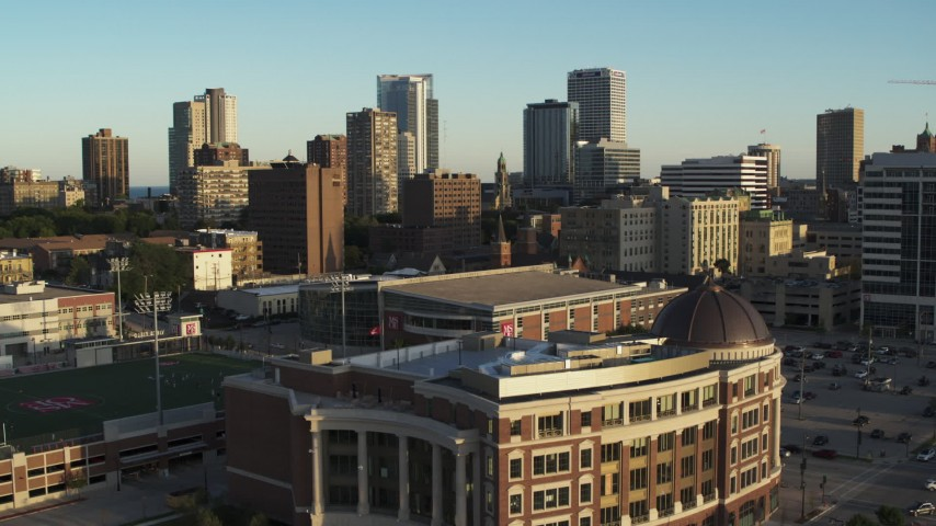 5.7K stock footage aerial video of ascending from a college building for a view of the skyline at sunset in Downtown Milwaukee, Wisconsin Aerial Stock Footage | DX0002_150_014