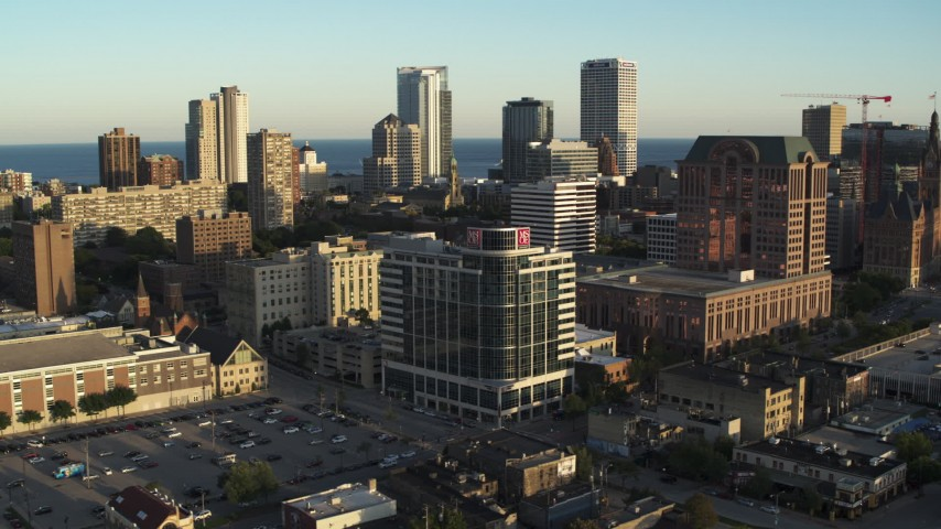 5.7K stock footage aerial video passing dormitory building for view of the city's skyline at sunset, Downtown Milwaukee, Wisconsin Aerial Stock Footage | DX0002_150_016