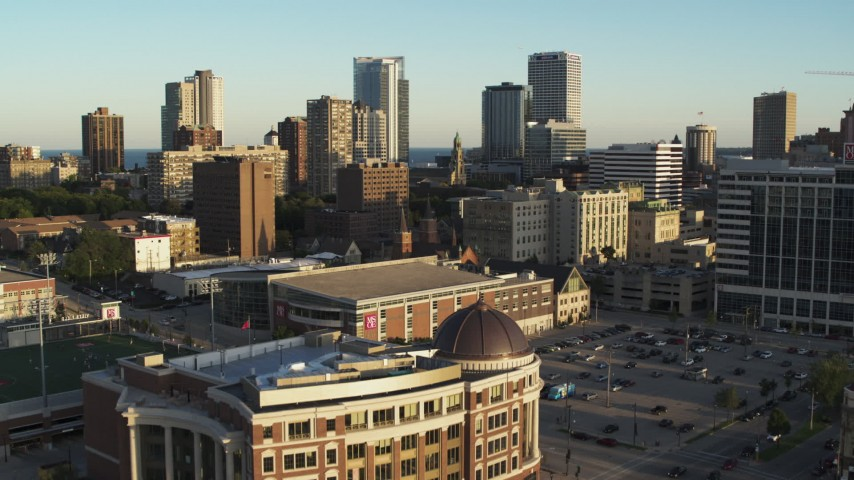 5.7K stock footage aerial video fly over college campus at sunset to approach city skyline, Downtown Milwaukee, Wisconsin Aerial Stock Footage   DX0002_150_020