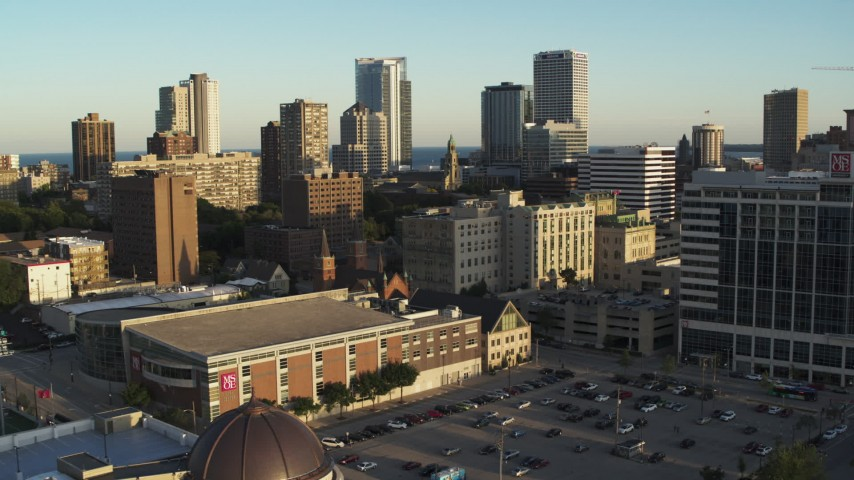 5.7K stock footage aerial video ascend away from college campus at sunset with view of city skyline, Downtown Milwaukee, Wisconsin Aerial Stock Footage | DX0002_150_022