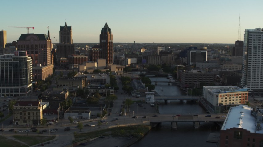 5.7K stock footage aerial video of city buildings and an office tower by the Milwaukee River at sunset, Downtown Milwaukee, Wisconsin Aerial Stock Footage | DX0002_150_027