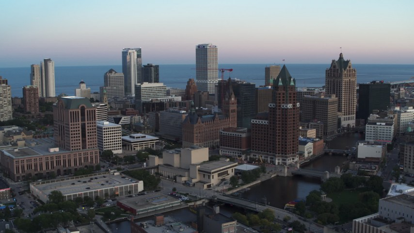 5.7K stock footage aerial video city buildings and skyscrapers seen from Milwaukee River at twilight, Downtown Milwaukee, Wisconsin Aerial Stock Footage | DX0002_150_029