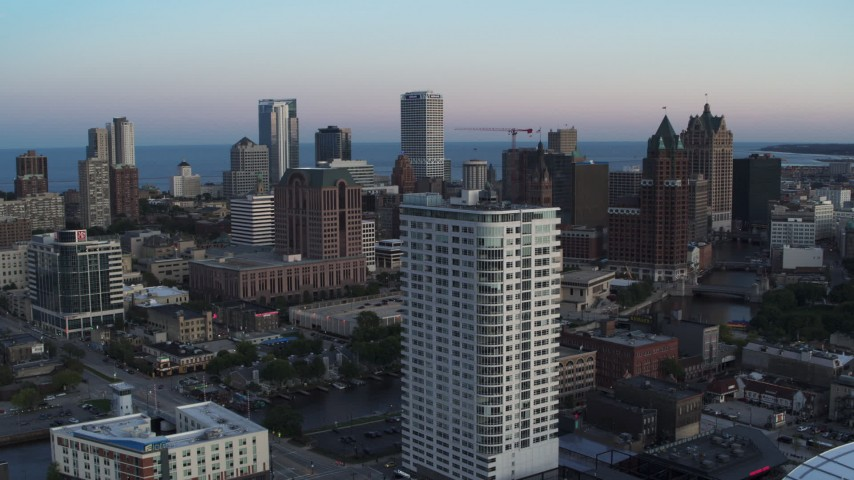 5.7K stock footage aerial video descend by apartment complex with view of downtown at twilight, Downtown Milwaukee, Wisconsin Aerial Stock Footage | DX0002_150_030