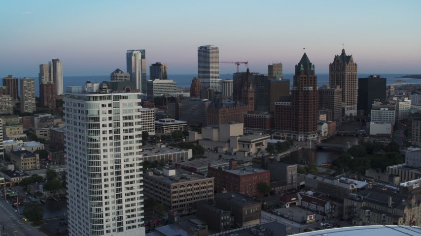 5.7K stock footage aerial video flying by apartment complex for view of downtown at twilight, Downtown Milwaukee, Wisconsin Aerial Stock Footage | DX0002_150_031