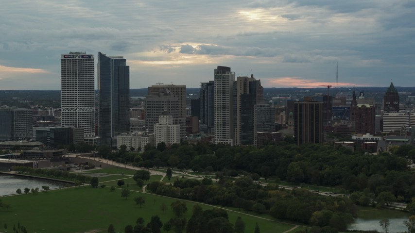 5.7K stock footage aerial video of tall skyscrapers in the city's skyline seen from green park at sunset, Downtown Milwaukee, Wisconsin Aerial Stock Footage | DX0002_155_013