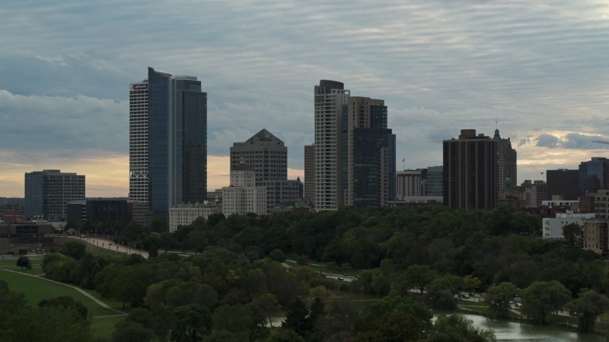5.7K stock footage aerial video descend toward park with view of tall skyscrapers in the city's skyline at sunset, Downtown Milwaukee, Wisconsin Aerial Stock Footage | DX0002_155_015