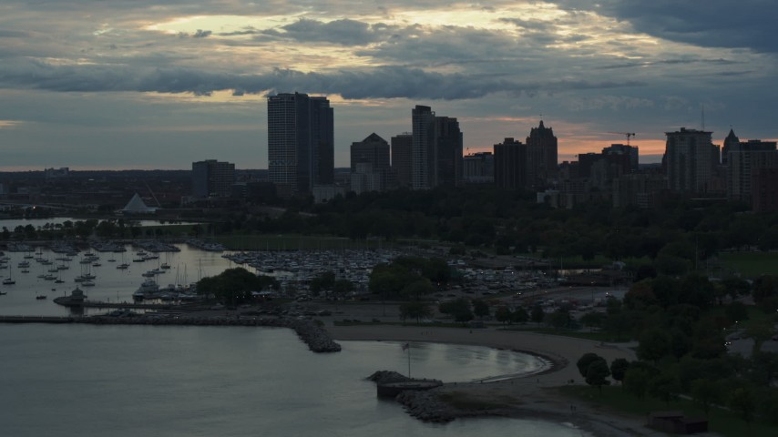 5.7K stock footage aerial video of skyscrapers in the city's skyline seen from the marina at sunset, Downtown Milwaukee, Wisconsin Aerial Stock Footage | DX0002_155_020