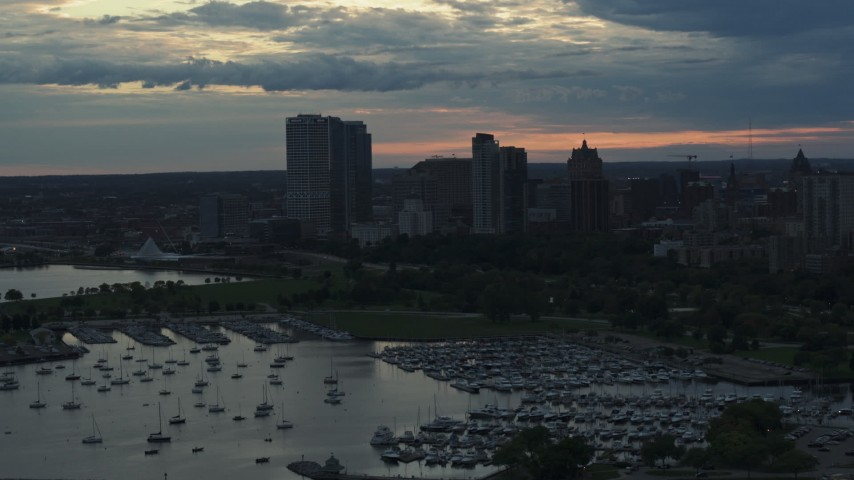 5.7K stock footage aerial video of skyscrapers in the city's skyline seen while ascending past the marina at sunset, Downtown Milwaukee, Wisconsin Aerial Stock Footage | DX0002_155_021