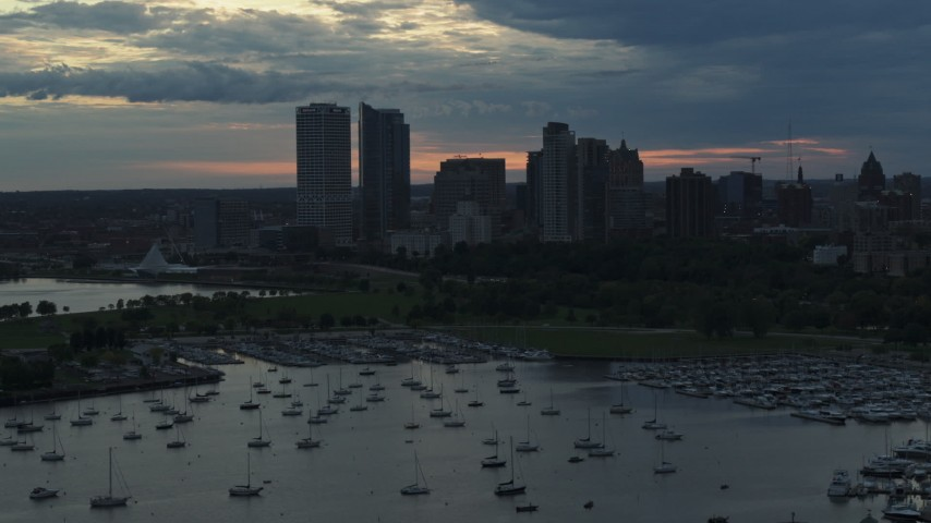 5.7K stock footage aerial video of skyscrapers in the city's skyline seen while descending past the marina at sunset, Downtown Milwaukee, Wisconsin Aerial Stock Footage | DX0002_155_022