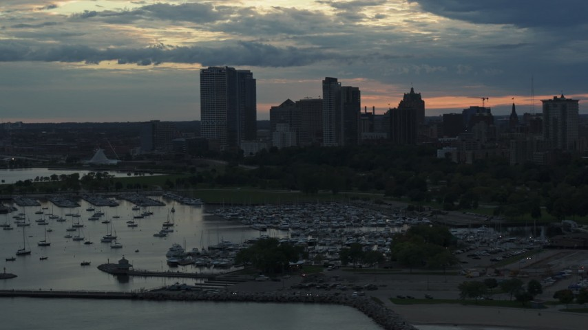 5.7K stock footage aerial video of skyscrapers in the city's skyline seen from a marina at sunset, Downtown Milwaukee, Wisconsin Aerial Stock Footage | DX0002_155_023