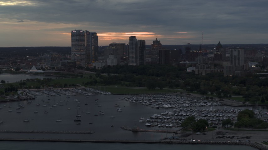 5.7K stock footage aerial video of skyscrapers in the city's skyline seen while ascending near marina at twilight, Downtown Milwaukee, Wisconsin Aerial Stock Footage | DX0002_155_025