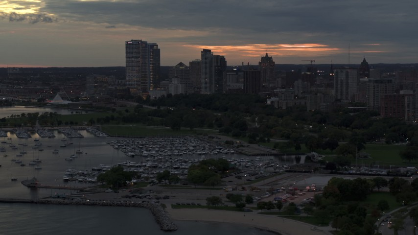 5.7K stock footage aerial video of skyscrapers in the city's skyline seen while passing the marina at twilight, Downtown Milwaukee, Wisconsin Aerial Stock Footage | DX0002_155_027