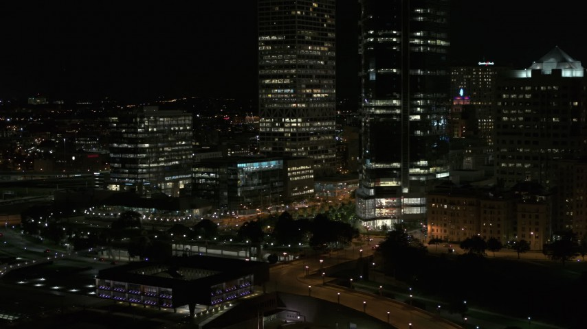 5.7K stock footage aerial video ascend and fly away from the base of a towering skyscraper at night, Downtown Milwaukee, Wisconsin Aerial Stock Footage | DX0002_157_037
