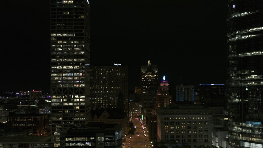 5.7K stock footage aerial video reverse view of Wisconsin Avenue and skyscrapers at night, Downtown Milwaukee, Wisconsin Aerial Stock Footage | DX0002_157_050