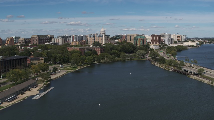 5.7K stock footage aerial video descend toward lake with view of of apartment buildings near the capitol dome in Madison, Wisconsin Aerial Stock Footage | DX0002_158_014