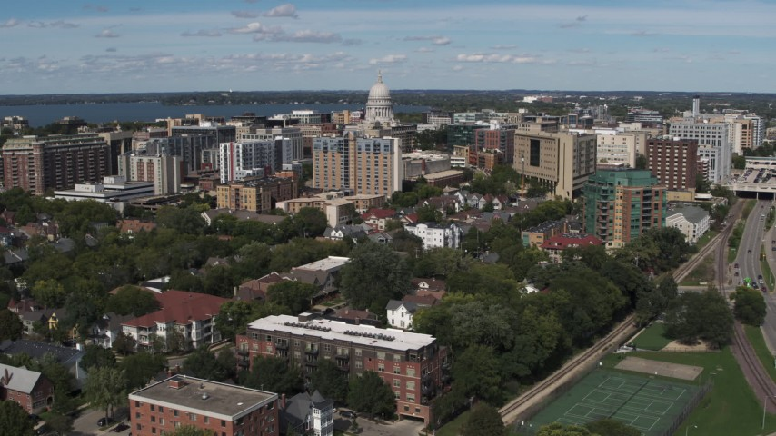 5.7K stock footage aerial video of a reverse view of apartment complexes around the capitol dome, then descend, Madison, Wisconsin Aerial Stock Footage | DX0002_158_022