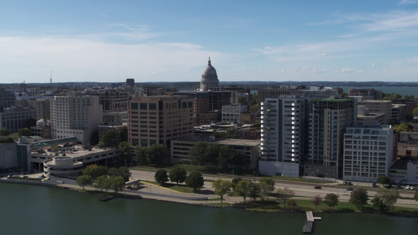 5.7K stock footage aerial video descend and fly away from the capitol dome surrounded by office buildings, Madison, Wisconsin Aerial Stock Footage | DX0002_158_029