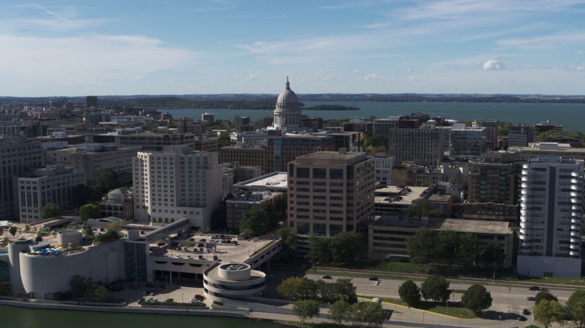 5.7K stock footage aerial video reverse view of capitol dome, office buildings, seen from lake, Madison, Wisconsin Aerial Stock Footage | DX0002_158_034