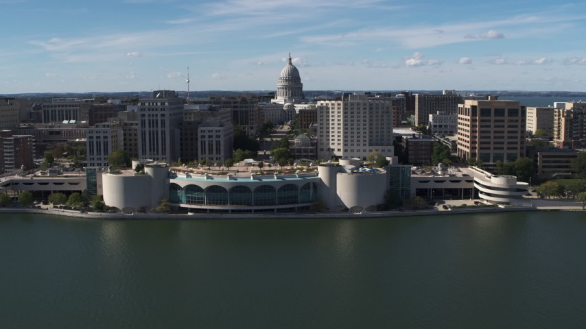 5.7K stock footage aerial video of the capitol dome and office buildings, seen while passing convention center, Madison, Wisconsin Aerial Stock Footage | DX0002_158_035