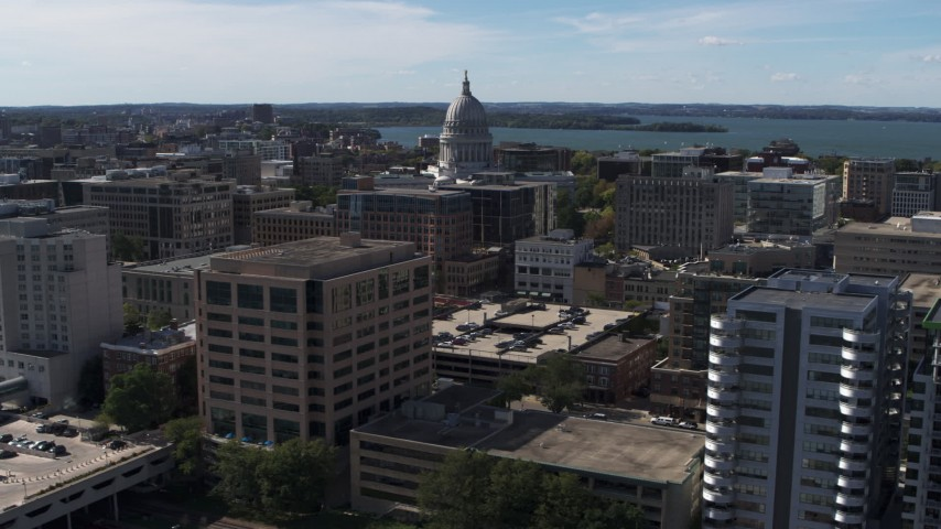 5.7K stock footage aerial video of the capitol dome seen while passing office buildings, Madison, Wisconsin Aerial Stock Footage | DX0002_158_038