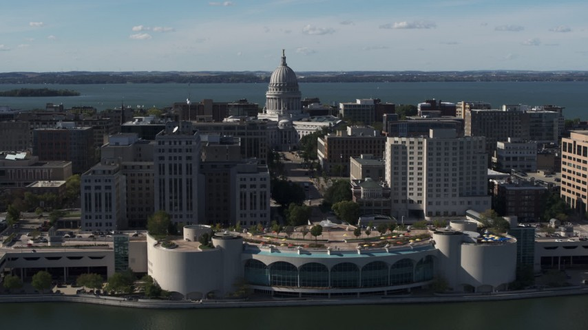 5.7K stock footage aerial video of the capitol seen while passing by office buildings and convention center, Madison, Wisconsin Aerial Stock Footage | DX0002_160_003