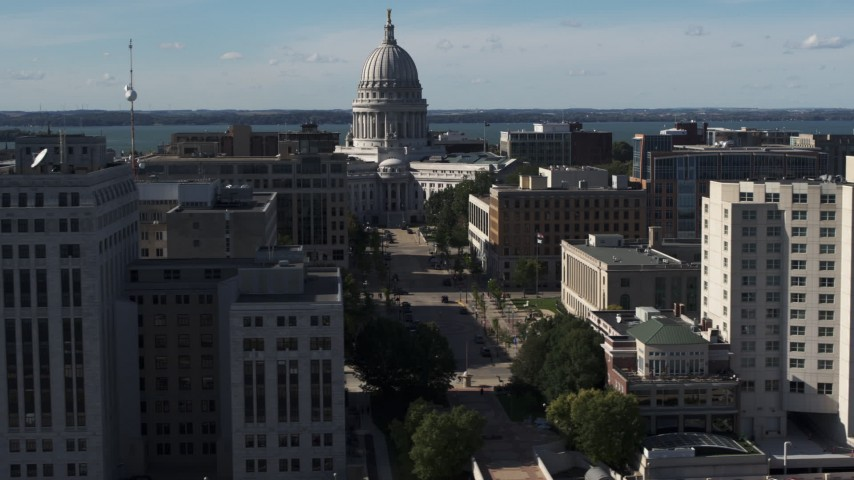 5.7K stock footage aerial video focus on the capitol building while passing office buildings, Madison, Wisconsin Aerial Stock Footage | DX0002_160_016