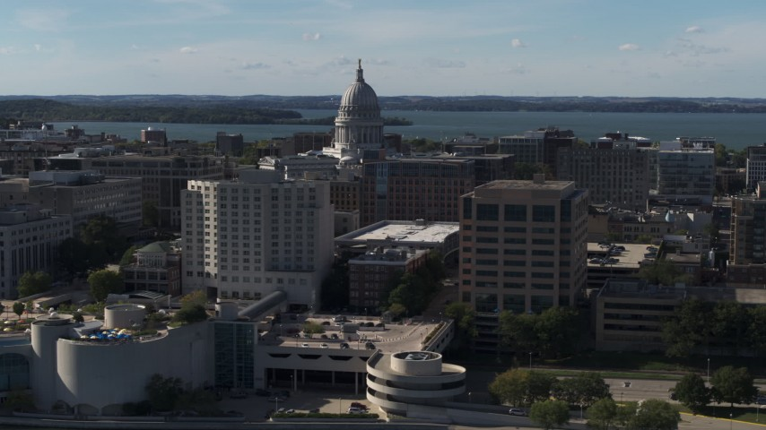 5.7K stock footage aerial video pass by convention center and office buildings and focus on the capitol building in Madison, Wisconsin Aerial Stock Footage | DX0002_160_018
