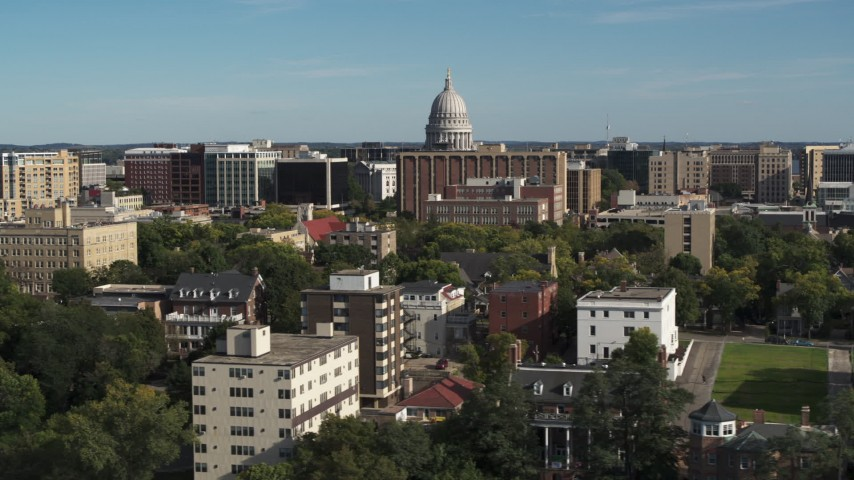 5.7K stock footage aerial video of flying by apartment buildings with a view of the capitol building in Madison, Wisconsin Aerial Stock Footage | DX0002_160_021