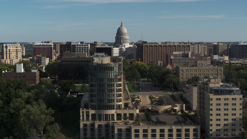 5.7K stock footage aerial video of flying by apartment buildings with a view of the capitol building, reveal hotel in Madison, Wisconsin Aerial Stock Footage | DX0002_160_022