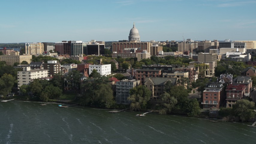 5.7K stock footage aerial video focus on the capitol dome while flying away from lakeside apartment buildings in Madison, Wisconsin Aerial Stock Footage | DX0002_160_026