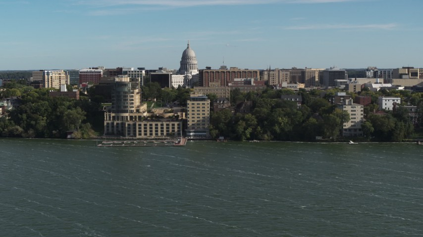 5.7K stock footage aerial video focus on the capitol dome while flying past a lakeside hotel in Madison, Wisconsin Aerial Stock Footage | DX0002_160_027