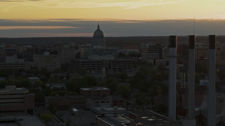 5.7K stock footage aerial video focus on the capitol dome at sunset while passing smoke stacks, Madison, Wisconsin Aerial Stock Footage | DX0002_161_027