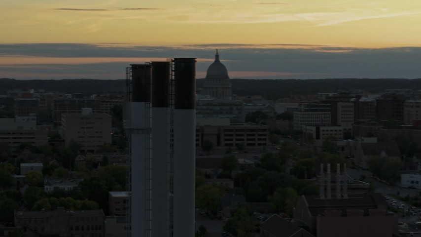 5.7K stock footage aerial video flyby the capitol dome at sunset, reveal and orbit smoke stacks, Madison, Wisconsin Aerial Stock Footage | DX0002_161_029