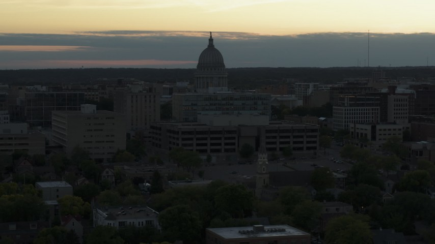 5.7K stock footage aerial video approach and flyby the capitol dome at sunset, reveal smoke stacks, Madison, Wisconsin Aerial Stock Footage | DX0002_161_031