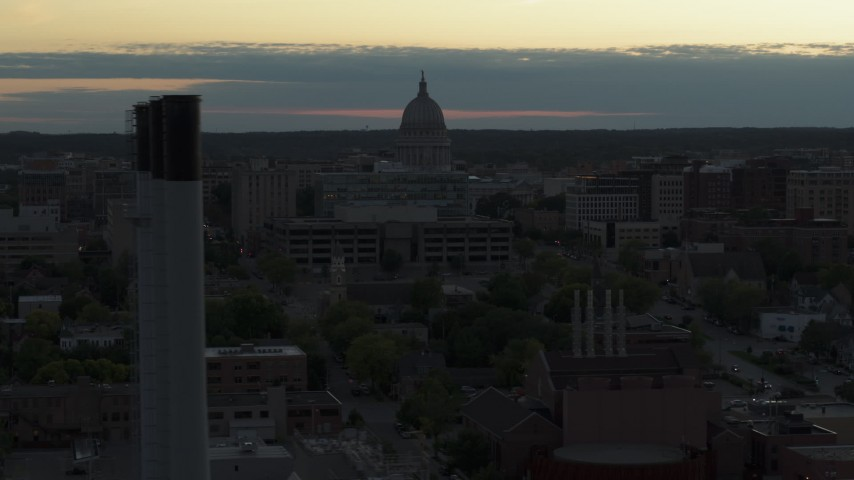 5.7K stock footage aerial video of passing the capitol dome at sunset, reveal and orbit smoke stacks, Madison, Wisconsin Aerial Stock Footage | DX0002_162_002