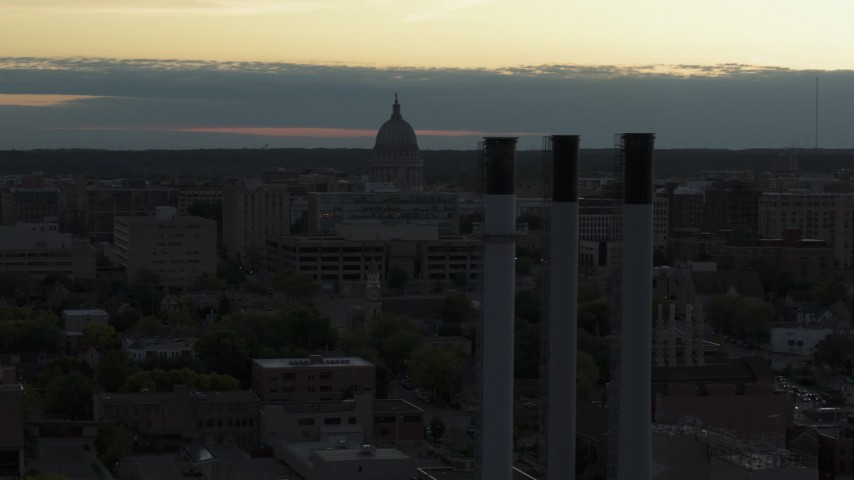 5.7K stock footage aerial video focus on the capitol dome at sunset, reveal and fly away from smoke stacks, Madison, Wisconsin Aerial Stock Footage | DX0002_162_003