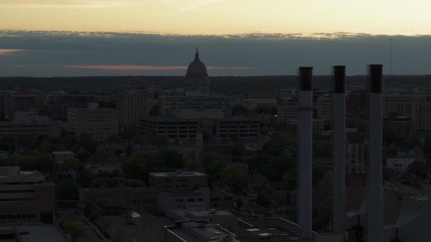 5.7K stock footage aerial video flyby smoke stacks to approach the capitol dome at sunset, Madison, Wisconsin Aerial Stock Footage | DX0002_162_004