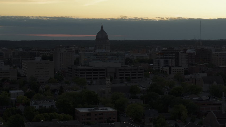 5.7K stock footage aerial video reveal smoke stacks while flying away from the capitol dome at sunset, Madison, Wisconsin Aerial Stock Footage | DX0002_162_005